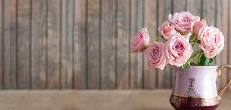 Hermosas rosas en una jarra vintage sobre fondo de madera rústica Foto de archivo - 78274586