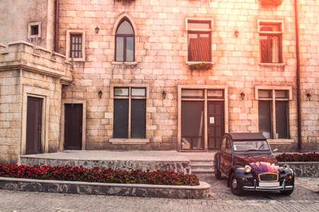 Old vintage cult car parked on the street by the ancient building Reklamní fotografie