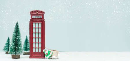 Banner with christmas decorations, toy red phone booth, trees, gifts on light background Banco de Imagens