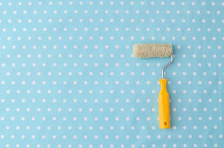yellow paint roller over blue polka dot wallpaper in nursery room