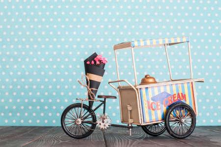 Chariot de crème glacée jouet vintage sur roues avec bouquet de fleurs