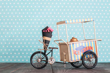 Vintage toy ice cream cart on wheels with bunch of flowers 스톡 콘텐츠
