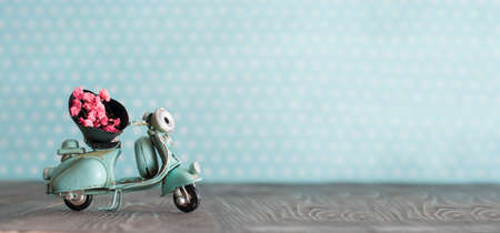 Tiny vintage toy blue mototrcycle with bunch of pink flowers on wooden table in nursery room