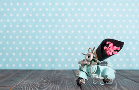 Vintage toy blue mototrcycle with bunch of pink flowers on wooden table in nursery room