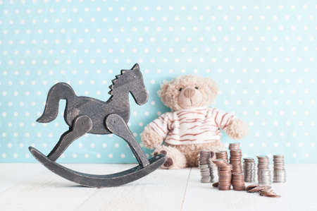 Toy horse, teddy bear and money change in child's room. spending money on children.