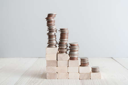Piles of coins standing on wooden stairs on daylight room Foto de archivo - 117939756