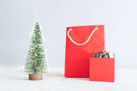 Red shopping bag and gift box with coins on the christmas tree Foto de archivo - 117939736