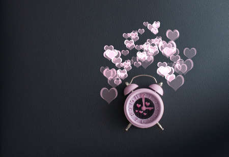 It's love o'clock. Valentine's pink alarm with heart shaped symbols on black leather Banco de Imagens - 117939737