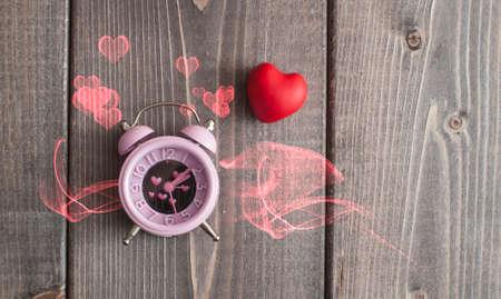 It's love o'clock. Valentine's pink alarm with heart shaped symbols on wooden Foto de archivo - 117939738