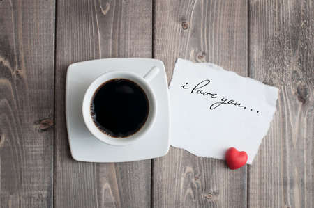 Cup of black coffee and love Valentine's day message with red heart shape on rustic wooden Foto de archivo - 117939735