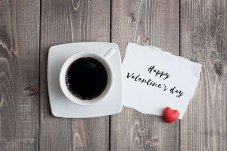 Cup of black coffee and Valentine's day greeting card with red heart shape on rustic wooden Foto de archivo - 117939739