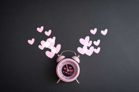It's love o'clock. Valentine's pink alarm with heart shaped symbols on black leather Foto de archivo - 117939742