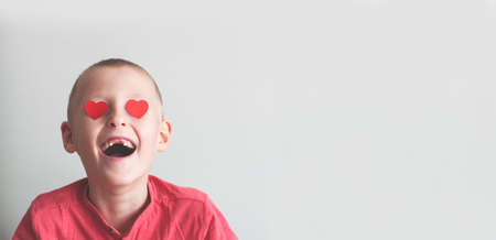 Happy boy with heart shape loving look on white Stock Photo