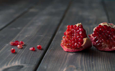 Red pomegranate with juicy seeds on wooden kitchen table Foto de archivo - 117939741