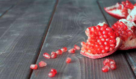 Red pomegranate with juicy seeds on wooden kitchen table Foto de archivo - 117939746