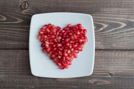 Red pomegranate seeds in shape of heart in a dish on wooden kitchen table Foto de archivo - 117939749
