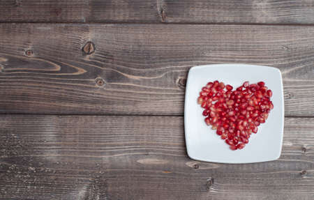 Red pomegranate seeds in shape of heart in a dish on wooden kitchen table Foto de archivo - 117939752