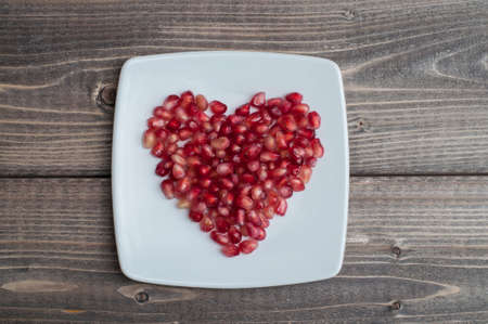 Red pomegranate juicy seeds in shape of heart in a dish on wooden kitchen table Foto de archivo - 117939751