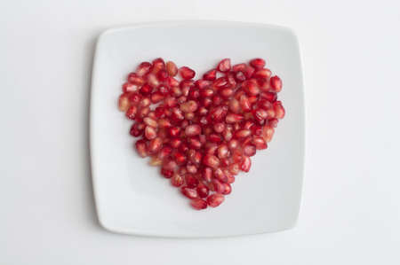 Red pomegranate juicy seeds in shape of heart in a dish on white kitchen table Foto de archivo - 117939747