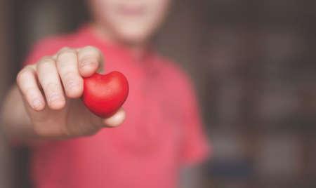 Boy holding red heart shape in his hand Foto de archivo - 117939754