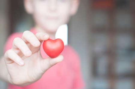Boy holding red heart shape in his hand Foto de archivo - 117939753