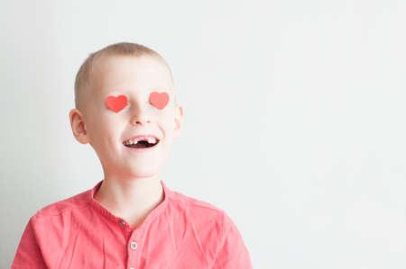 Happy boy with heart shape loving look on white Foto de archivo - 117939676