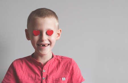 Happy boy with heart shape loving look on white Foto de archivo - 117939675