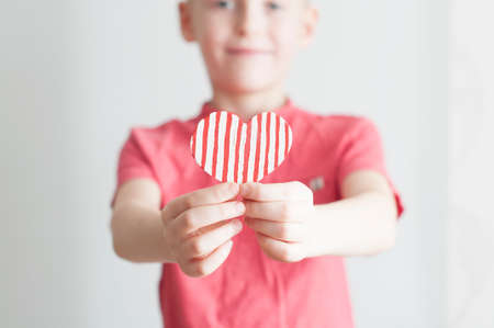 Happy boy giving red stripped heart shape to his mom on white Stock Photo