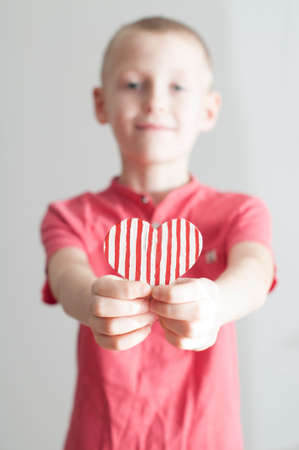 Happy boy giving red stripped heart shape to his mom on white Banco de Imagens
