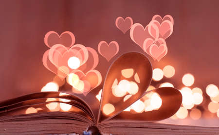 An open book with pages curved in shape of heart and bokeh light Foto de archivo - 117939683