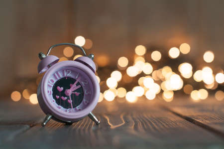 It's time for love. Valentine's pink alarm with heart shaped symbols on bokeh lights Foto de archivo - 117939686