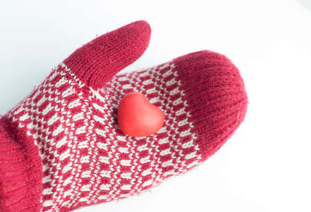 Human hand in mitten holding red heart shape outdoors on white winter Foto de archivo - 117939685
