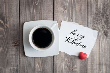 Cup of black coffee and love Valentine's day message with red heart shape on rustic wooden Foto de archivo - 117939689