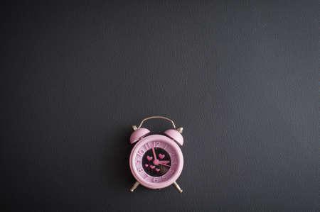 It's love o'clock. Valentine's pink alarm with heart shaped symbols on black leather Banco de Imagens - 117939692