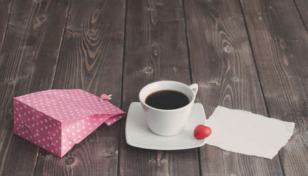 Cup of black coffee, pink paper bag and love Valentine's day message with red heart shape on rustic wooden Foto de archivo - 117939691