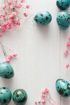 Easter quail eggs with flowers on white wooden background
