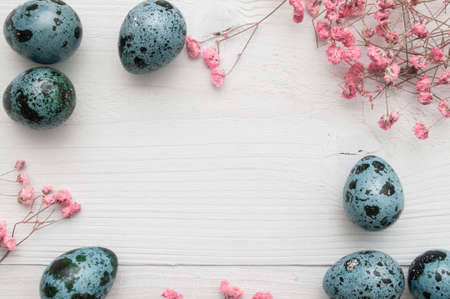 Easter quail eggs with flowers on white wooden background Stock Photo - 128316237