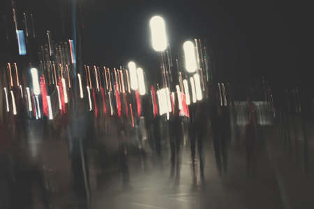 Abstract picture with defocused night street lights and people walking like ghosts
