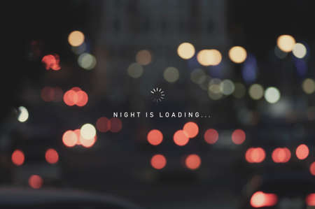 Night is loading sign on defocused blur of city street lights at night abstract background