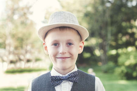 Smiling boy in vest, hat and bowtie looking at camera in the park Stockfoto