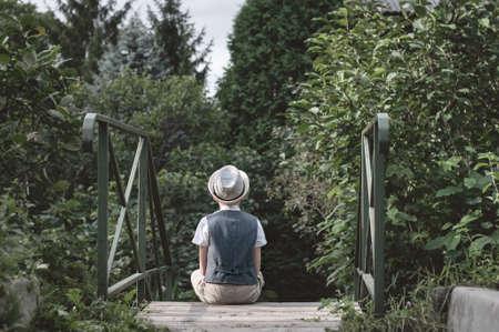 Little kid sitting alone on a stairs in th garden Stock Photo