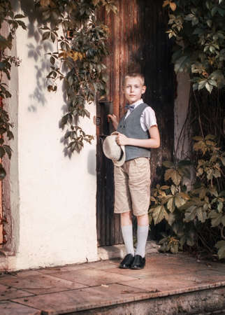 Boy with hat knocking on door in a countryside residence 写真素材