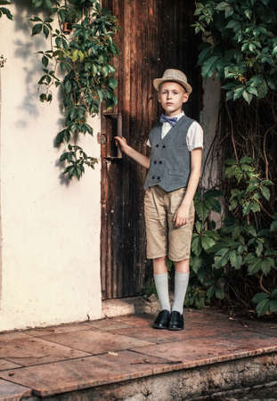Boy in hat stands near the door in a countryside residence