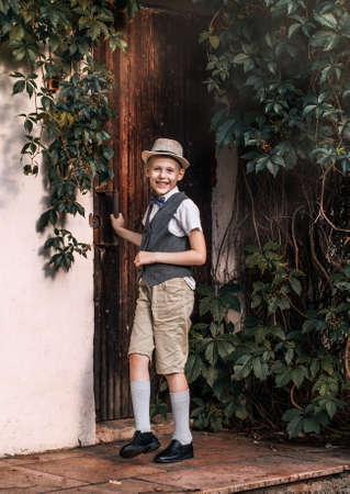 Boy in hat laughing near the door in a countryside residence 写真素材