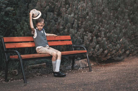 Retro portrait of child sitting at  the park bench in the countryside