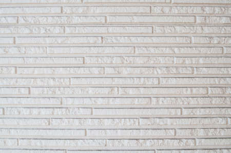 Background textured as finishing material of the wall made of imitation  of narrow white brick