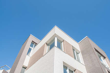 Modern minimalistic apartment building and blue sky
