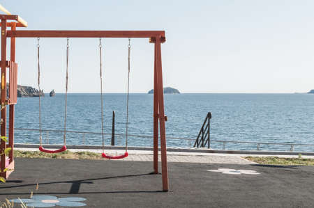 Childrens playground with red swing on seaside promenade