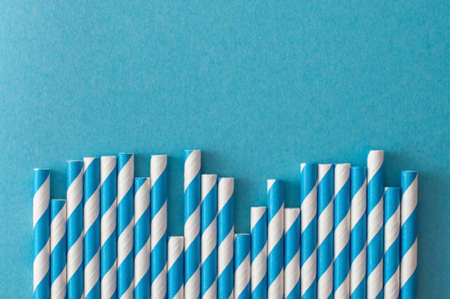 Monochrome swirled drinking straws on pastel blue background