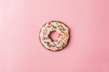 Donut cookie glazed and sprinkled on pink background
